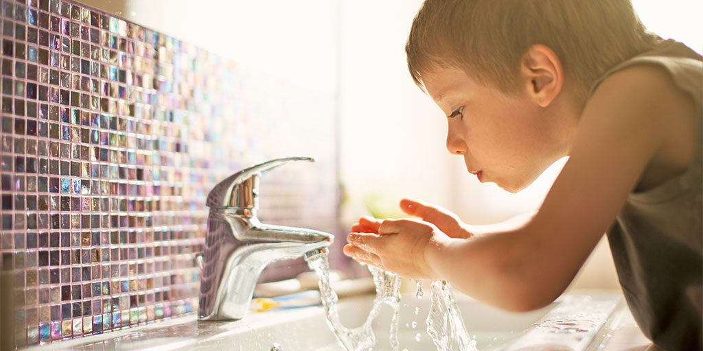 Enfant buvant l'eau du robinet dont on a enlever le calcaire, les pesticides et les nitrates